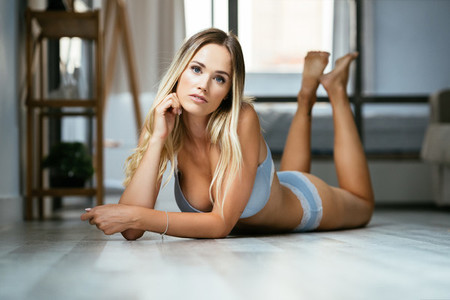 Caucasian girl in blue lingerie lying on the floor in her house