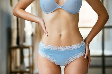 Unrecognizable woman with a beautiful belly wearing blue lingerie
