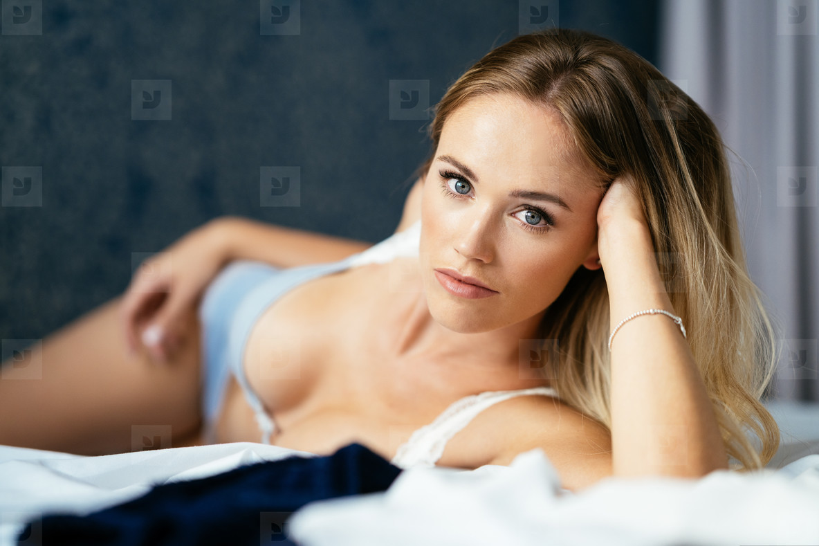 Young blond woman with amazing blue eyes laying on the bed wearing lingerie