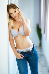 Young caucasian woman posing in blue bra and jeans