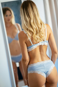 Caucasian girl in blue lingerie looking at herself in a wall mirror