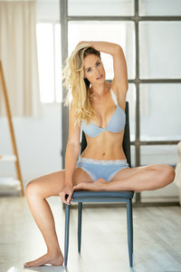 Young adult caucasian woman in blue lingerie sitting on a chair at home