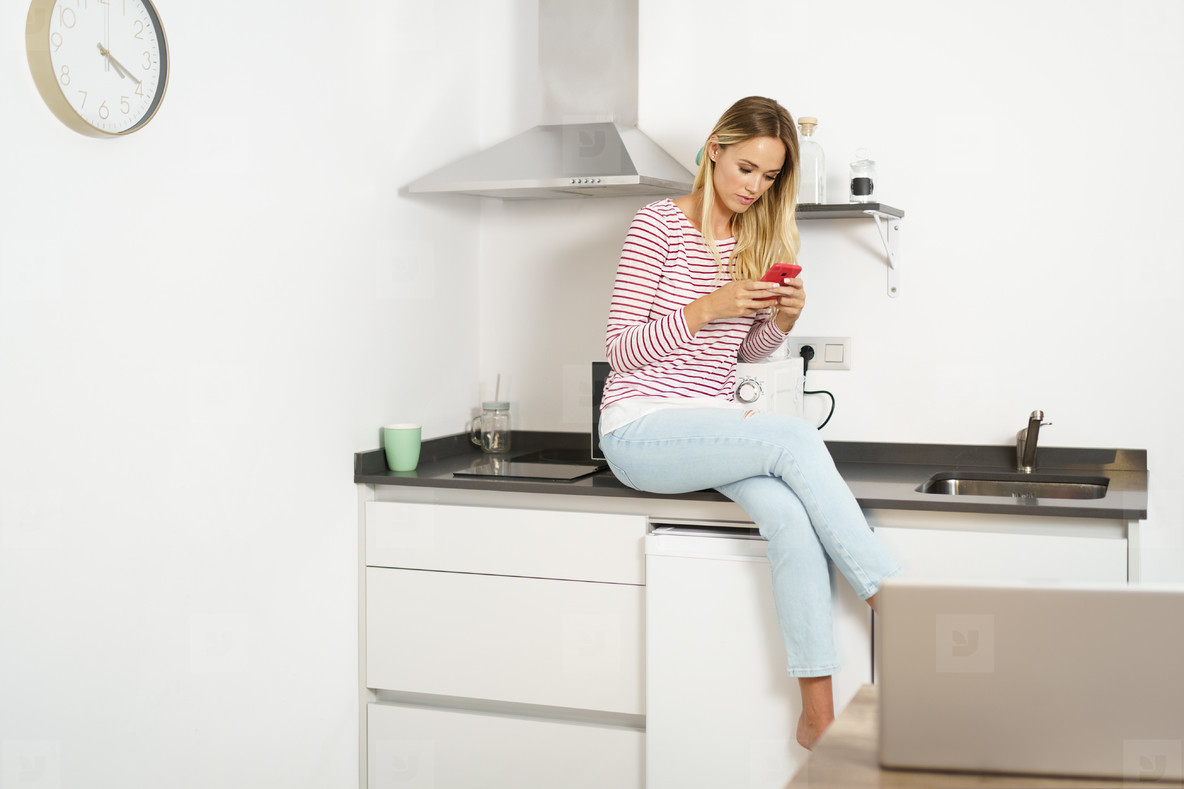 Thinking beautiful woman using her smartphone sitting in the kitchen at home