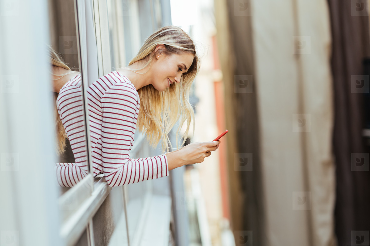 Caucasian woman leaning out of her house window using a smartphone