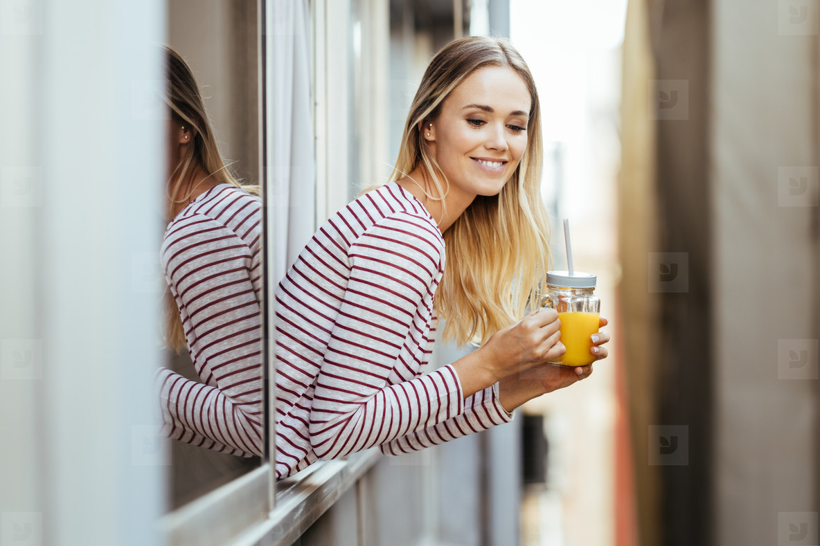 Smiling woman drinking a glass of natural orange juice  leaning out the window of her home