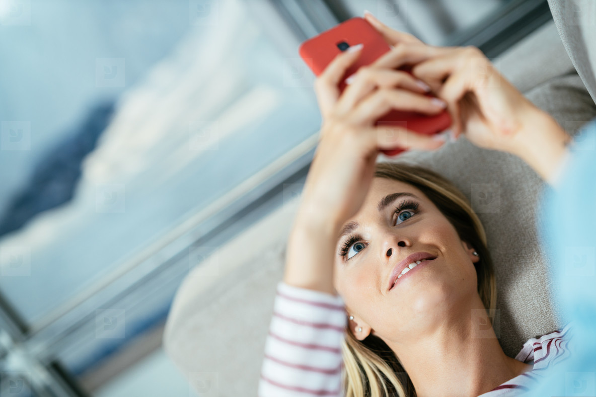 Close up of woman using her smartphone lying on the sofa