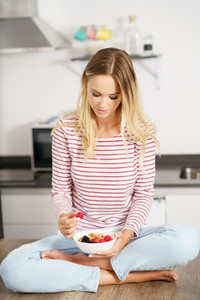 Caucasian woman eating an appetizer with nuts raspberries and blackberries