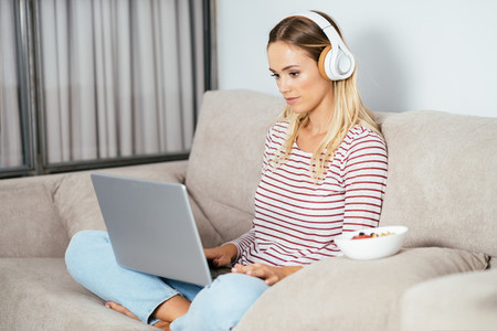 Young blonde woman with headphones and laptop on the sofa