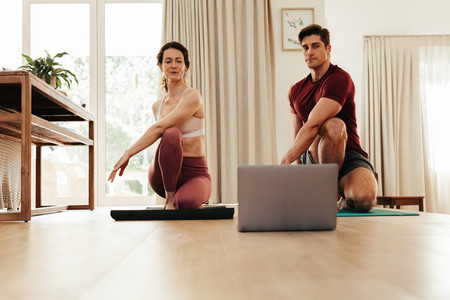 Couple going yoga watching fitness video on laptop