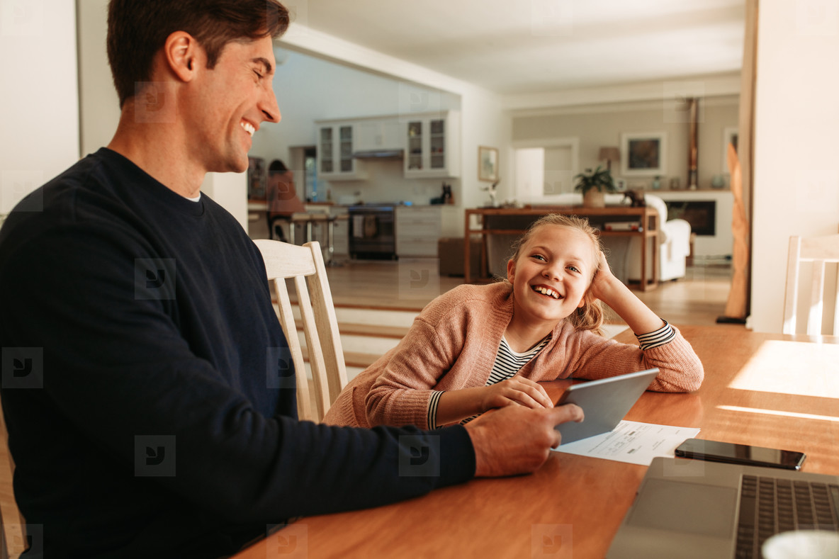 Smiling father and daughter at home with digital tablet
