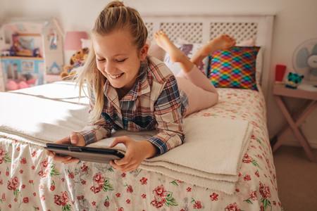 Girl in her room using digital tablet
