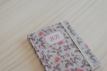 A 2021 diary on top of a light wooden desk