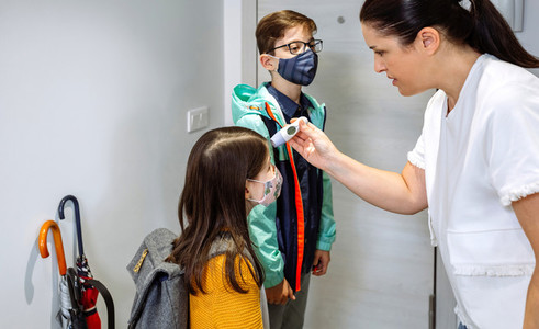 Mother checking her daughters temperature before going to school