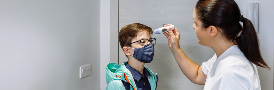 Mother checking her sons temperature before going to school