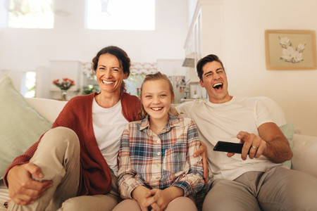 Family watching comedy movie on television