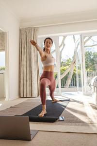 Woman training yoga watching online videos on laptop