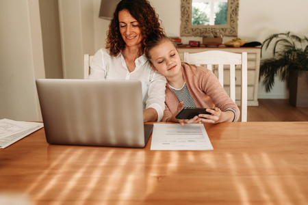 Mother working from home with daughter using smart phone