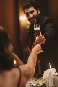 Handsome guy giving a champagne to a friend at dinner party