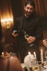 Man serving drinks to friends at dinner party
