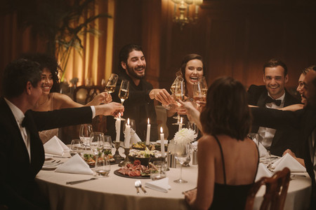 Multi ethnic people celebrating with drinks at dinner party
