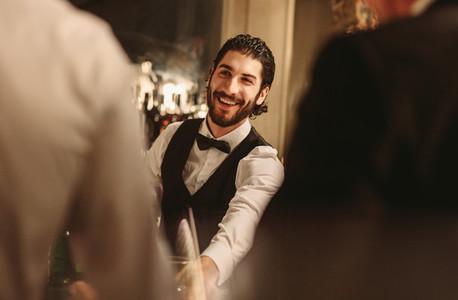 Smiling bartender serving drinks to guest