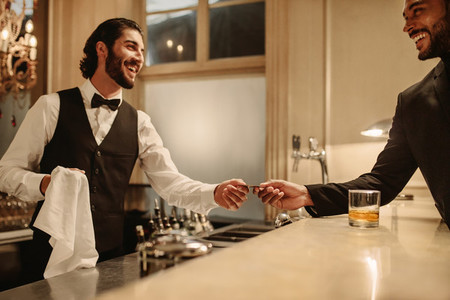 Bartender receiving credit card from a customer