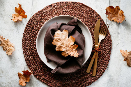 Top view of decorated table setting dish with fallen leaf Thanksgiving or Autumn festive dinner concept