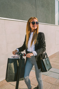 Woman with shopping bags on electric scooter