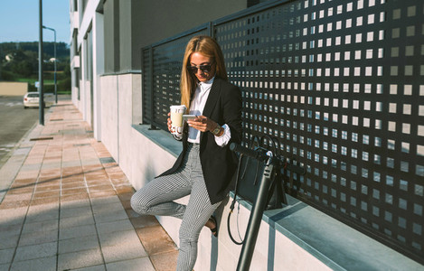 Businesswoman using mobile and drinking coffee with her scooter