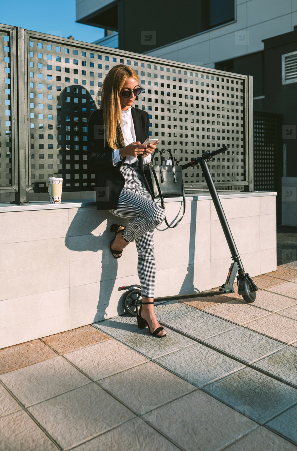 Businesswoman using mobile with her scooter next