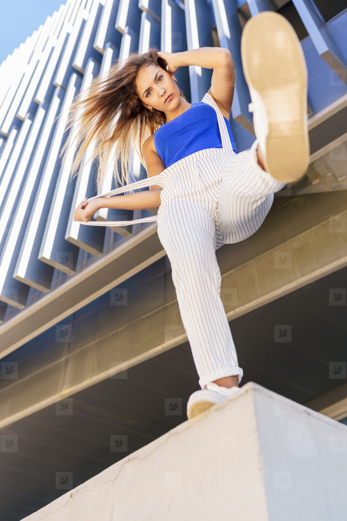 View from below of young girl throwing her foot in the air