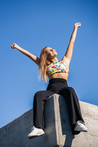 Young woman opening arms against blue sky
