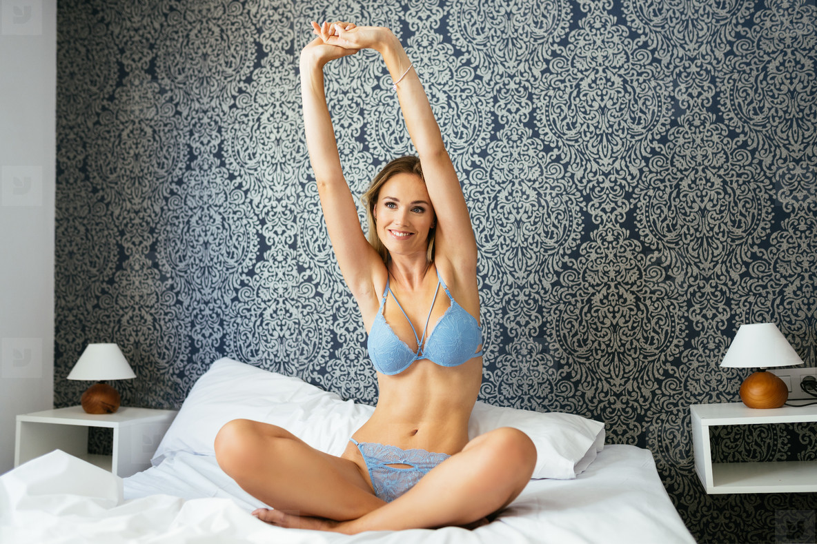 Caucasian blonde girl in blue lingerie stretching her body on the bed