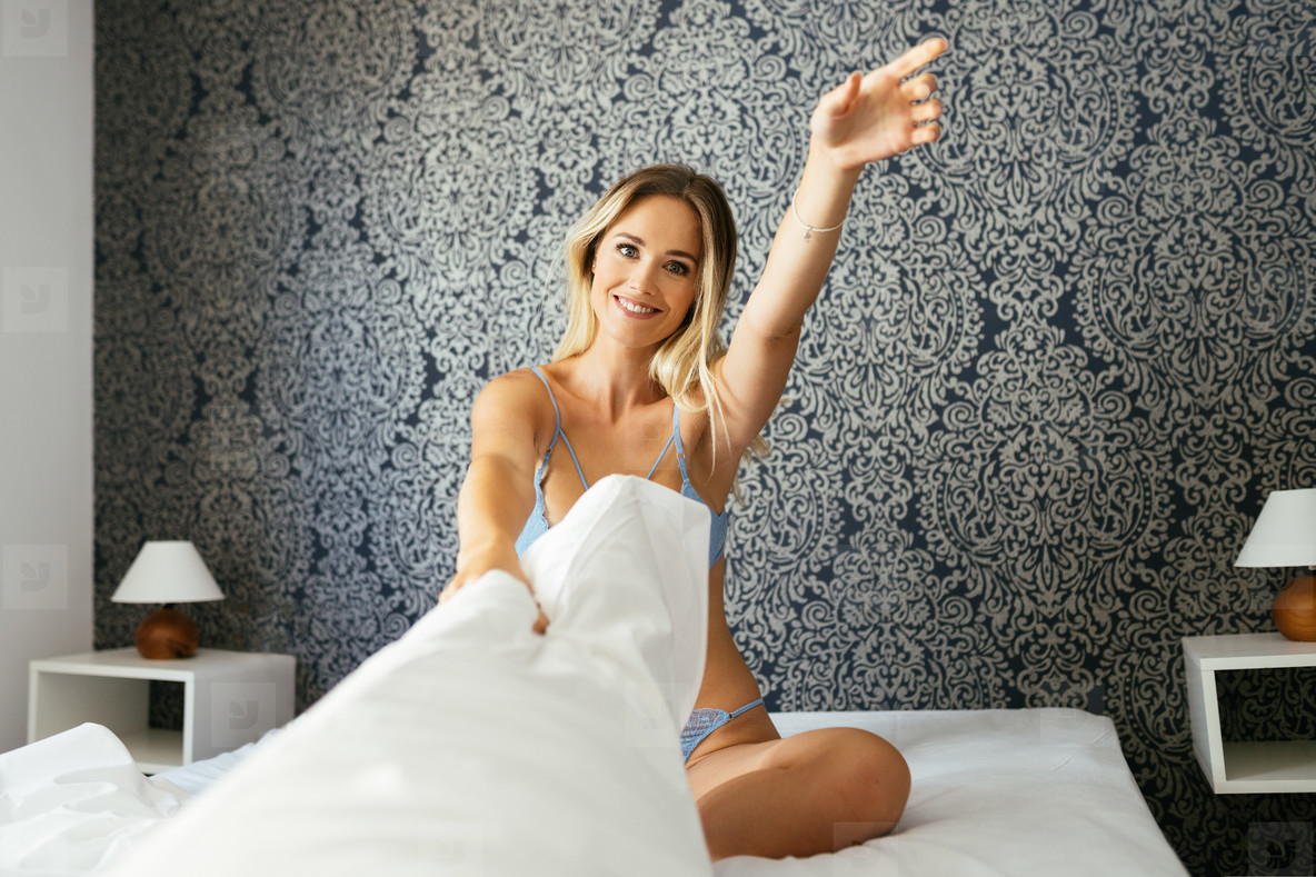 Funny girl in blue lingerie playing with her pillow on the bed