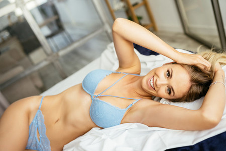 Smiling caucasian woman posing in blue lingerie lying on the bed