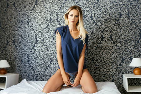 Young blond woman posing in her bed wearing a blue t shirt and panties