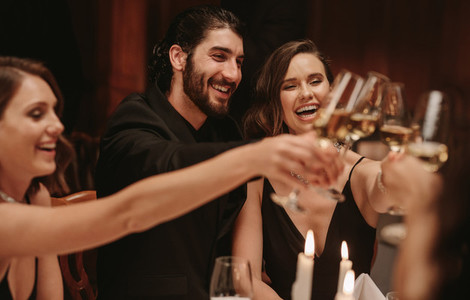 Multi ethnic people celebrating dinner party with drinks