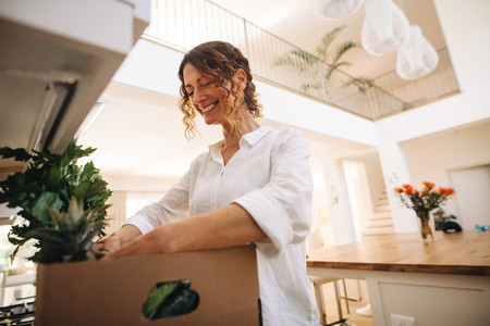 Smiling woman unpacking groceries