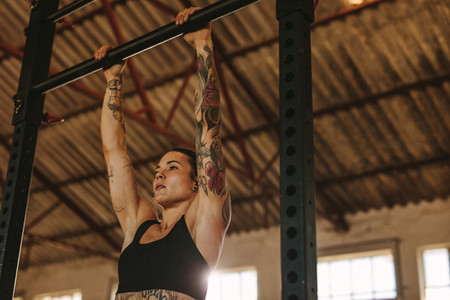 Woman doing pull up workout in fitness studio