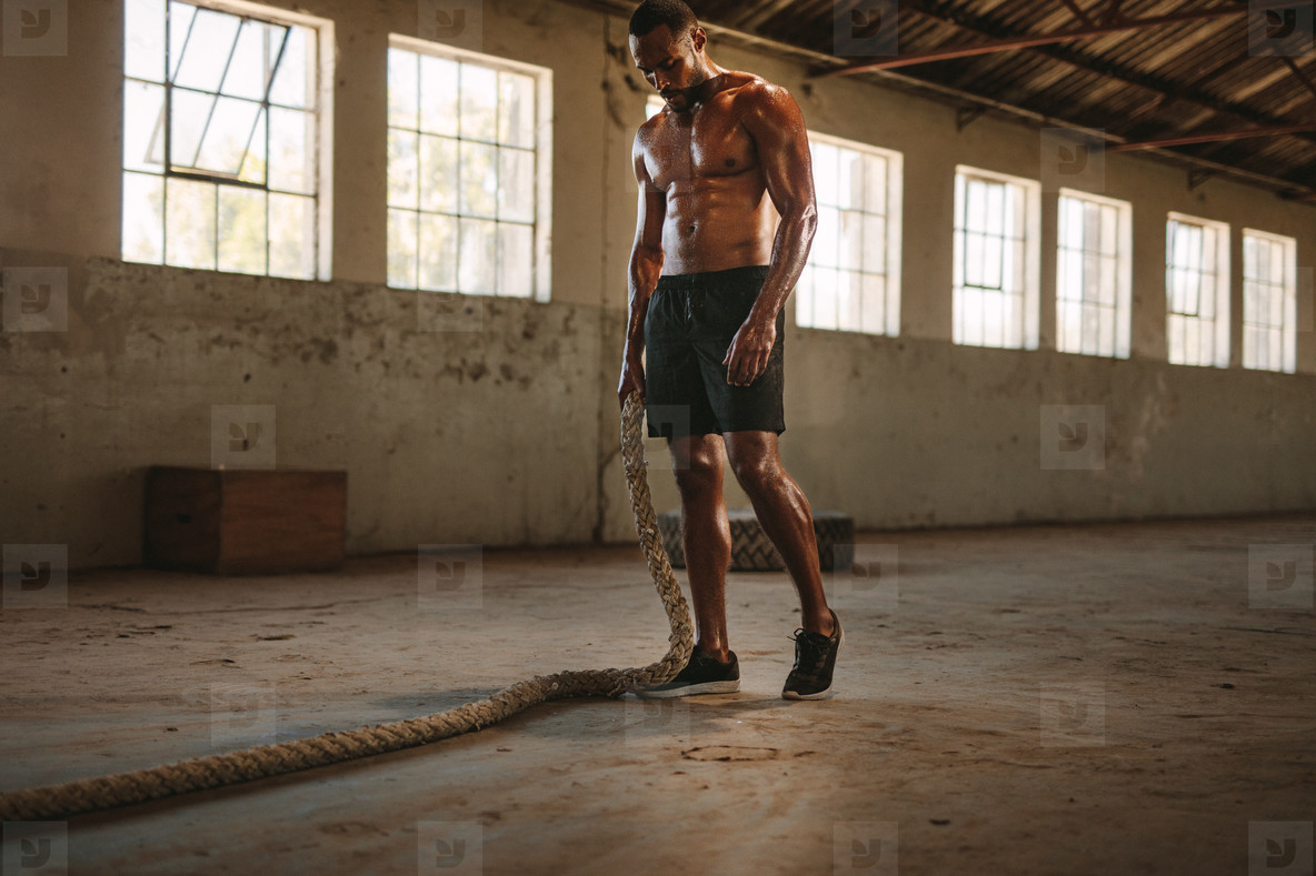 Muscular man in fitness studio with battle rope