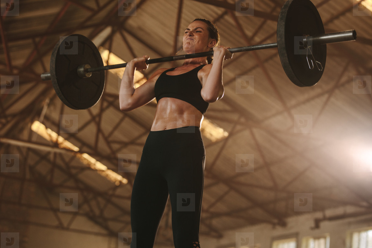 Tough woman doing snatch workout with barbell