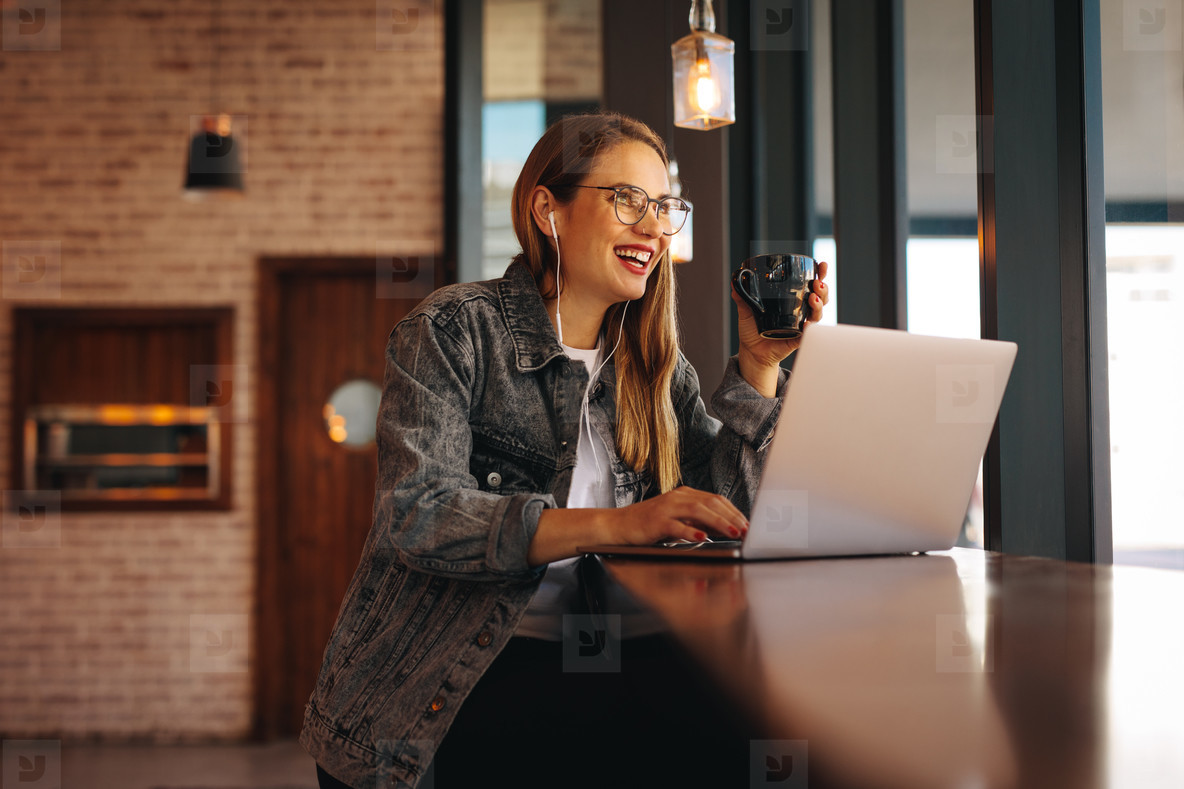 Woman enjoying working from a coffee shop