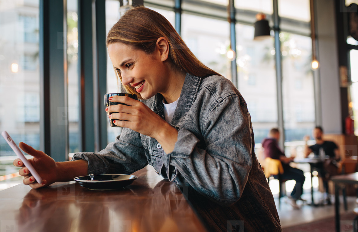Woman using phone at coffee shop
