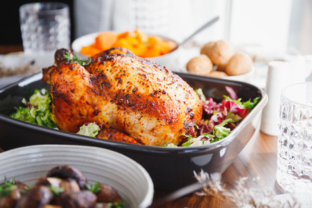 Whole roasted chicken served with fresh salad in black pan on a festive table Thanksgiving or family dinner celebration cooking concept