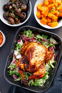 Top view of a whole roasted chicken served with fresh salad in black pan Thanksgiving or family dinner celebration cooking concept
