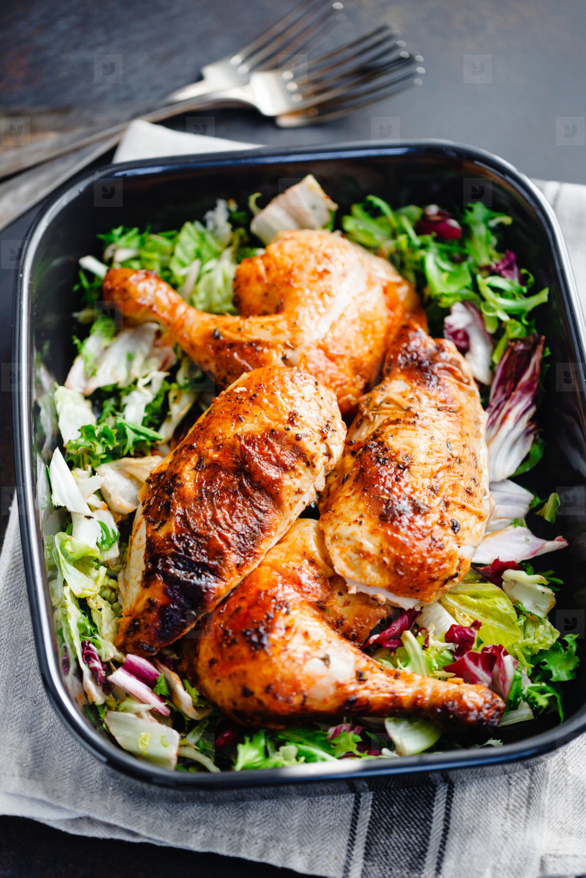 Top view of roasted chicken legs and breasts served with fresh salad and mushrooms in black pan