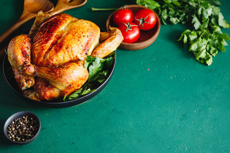 Whole roasted chicken and spices  Green background  place for text