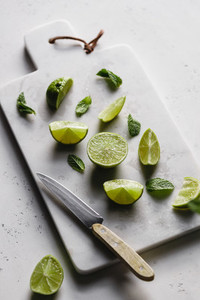 Cutted fresh lime on a white marble kitchen board with mint  Preparation beverage or food cooking concept