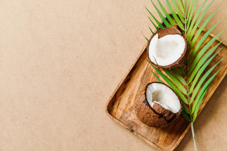 Summer abstract creative composition with coconut a on wooden tray and palm leaf over kraft paper