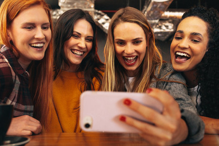 Friends having fun at cafe taking a selfie